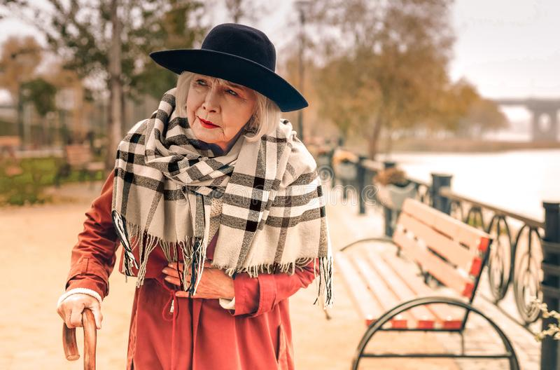 Senior stylish lady taking a walk in park suddenly experiencing chest pain royalty free stock images