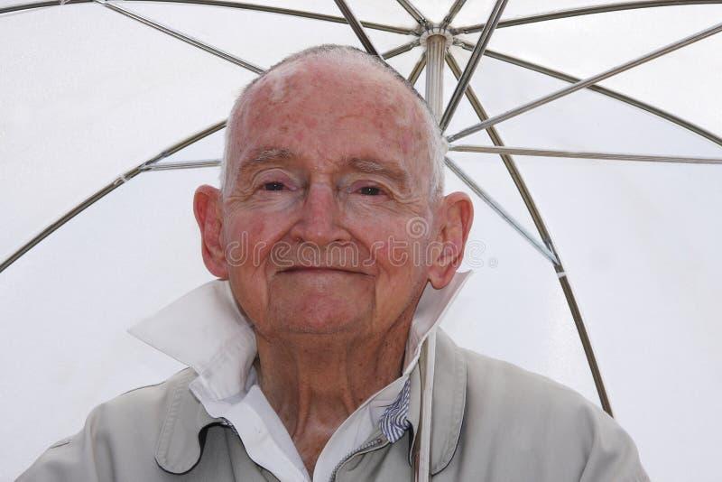 Senior in the sun. Senior man sitting under a white umbrella in the hot sun royalty free stock photos