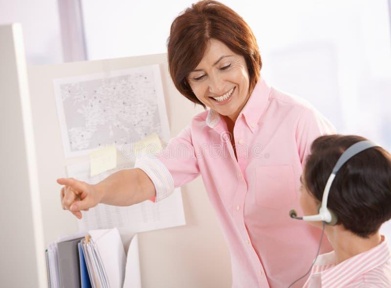 Senior supervisor helping customer care operator. Smiling senior supervisor helping customer care operator, pointing stock photography