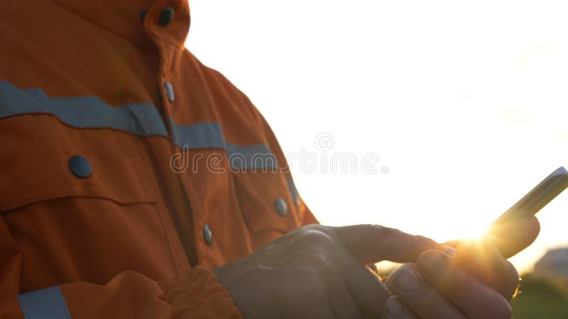 Senior surveyor in jumpsuit silhouette types on smartphone stock photos