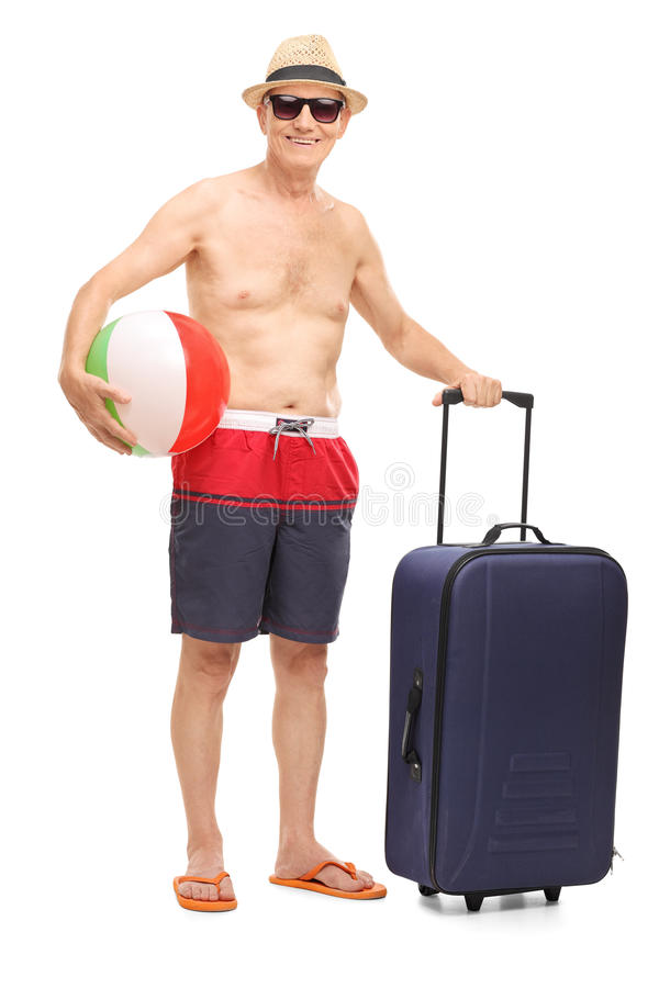 Senior in swim shorts holding a beach ball. Full length portrait of a senior in swim shorts holding a beach ball and a bag isolated on white background royalty free stock photography