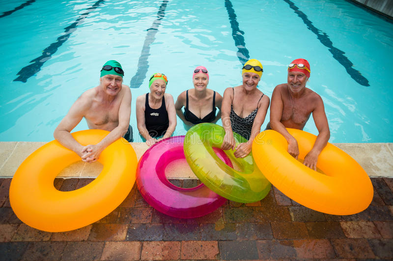 Senior swimmers with inflatable rings standing at poolside stock image