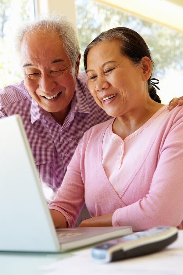 Senior Taiwanese couple working on laptop stock images