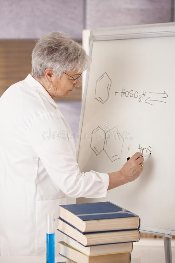 Download Senior Teacher Drawing Molecular Formulas Stock Photo - Image of board, hair: 18216168