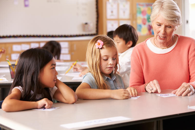 Senior teacher helping pupils in elementary school lesson royalty free stock image
