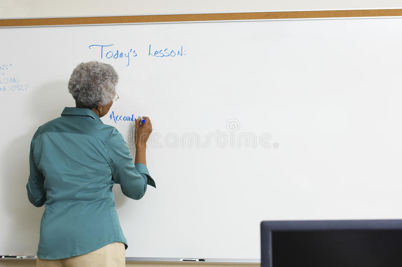 Senior Teacher Writing On Whiteboard stock images