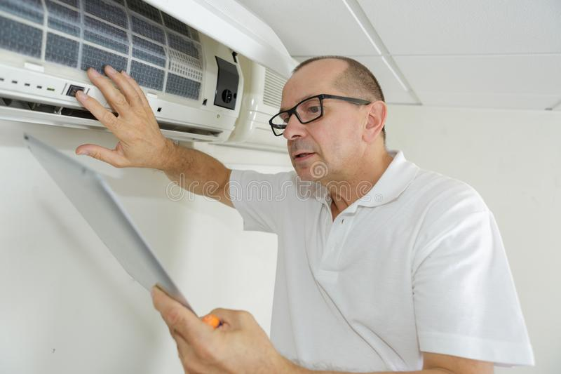 Senior technician with tablet by indoor air conditioning unit. Technician stock photo