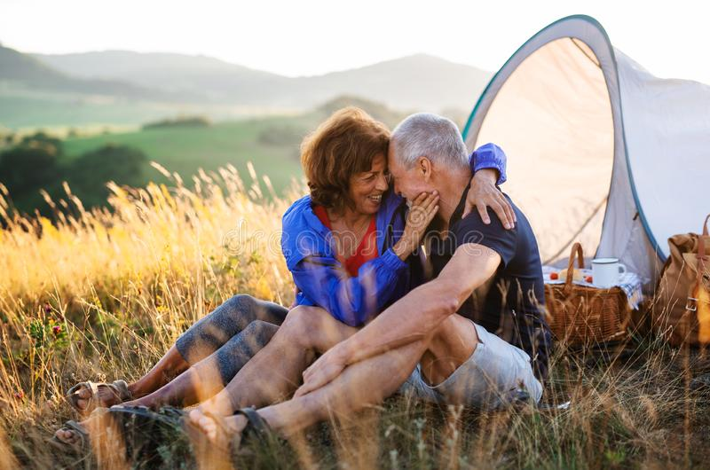 Senior tourist couple in love sitting in nature at sunset, resting. stock photo