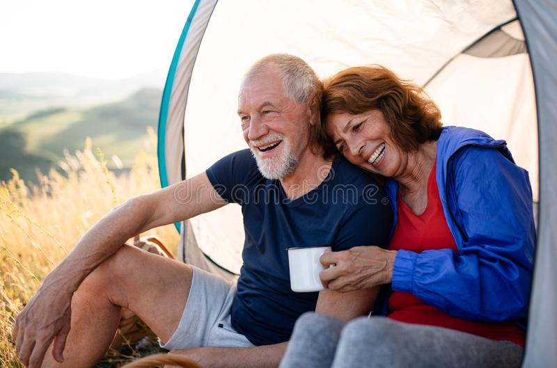 Senior tourist couple in love sitting in nature at sunset, resting. A senior tourist couple in love with shelter sitting in nature at sunset, resting royalty free stock image