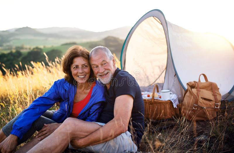Senior tourist couple in love sitting in nature at sunset, resting. stock photography