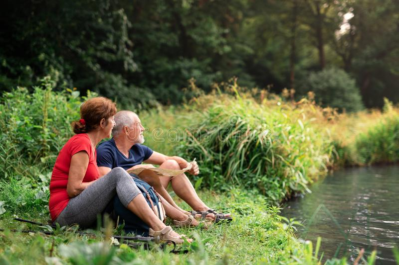 Senior tourist couple with map on a walk in nature, sitting by lake. Senior tourist couple with map on a walk in nature, sitting by lake and resting royalty free stock image