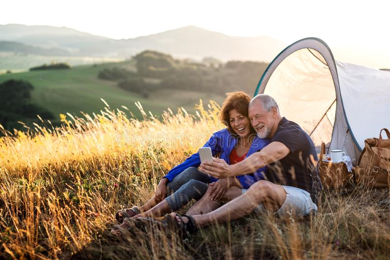 Senior tourist couple with smartphone sitting in nature at sunset, taking selfie. stock image