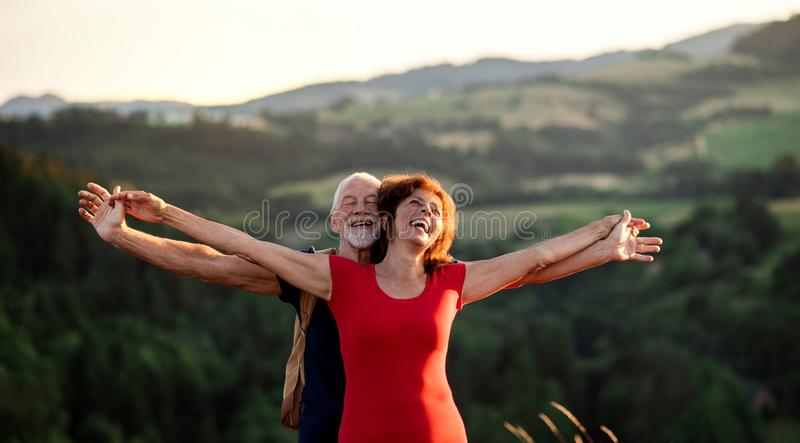 Senior tourist couple travellers with backpacks hiking in nature, resting. royalty free stock photo
