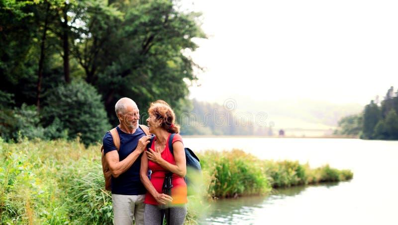 Senior tourist couple on a walk in nature, standing by lake. A senior tourist couple on a walk in nature, standing by lake. Copy space stock images