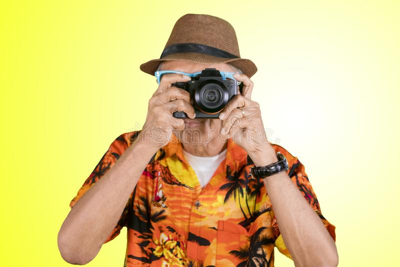 Senior traveler taking a picture in the studio. Close up of senior traveler using a digital camera to taking a picture while standing in the studio stock images