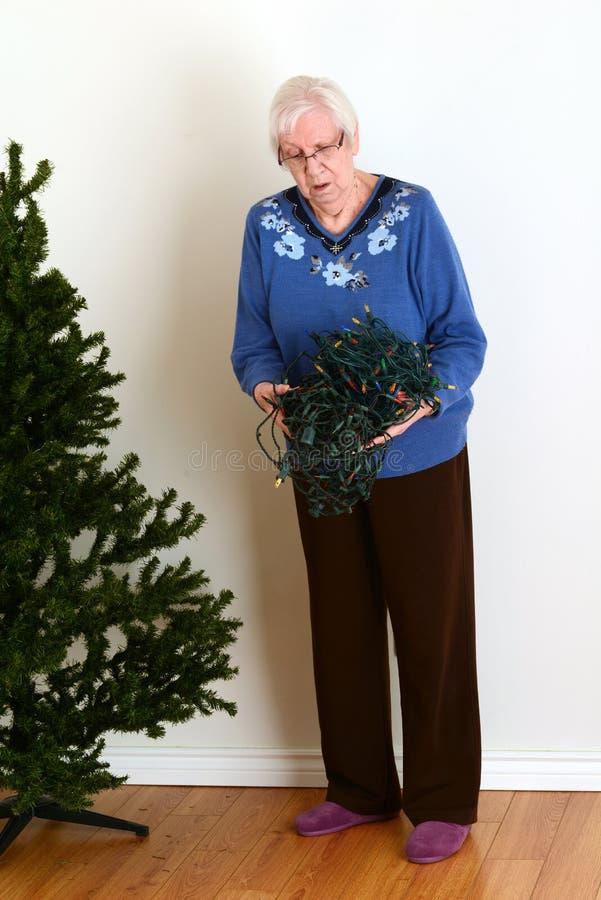 Free Senior Trying To Untangle Christmas Lights Stock Photos - 47129013
