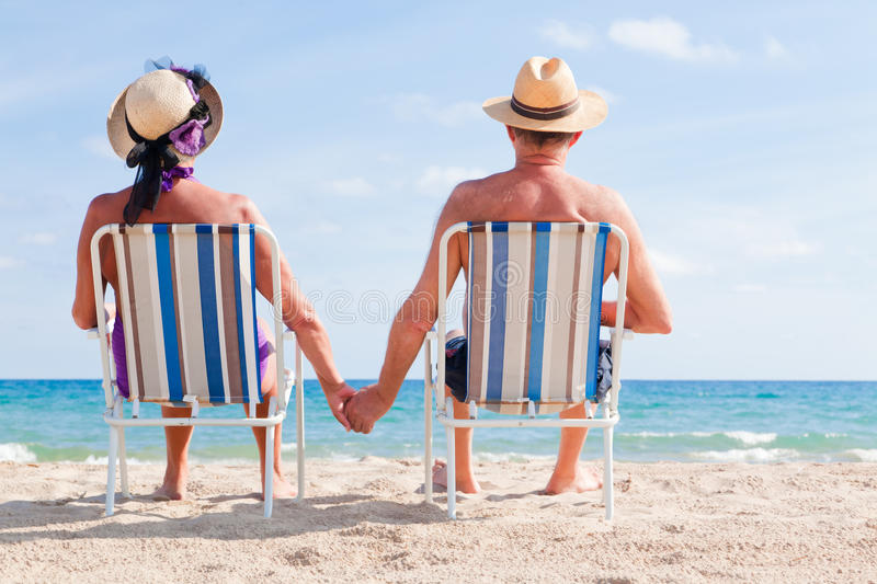 Senior vacation. Relaxed summer vacation senior couple of old man and woman sitting on the beach