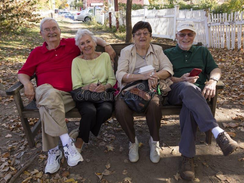 Senior vier sitzen auf Bank, West- Cornwall, das Housatonic-Fluss, West-Cornwall, Connecticut, USA am 18. Oktober 2016 übersieht stockfotos