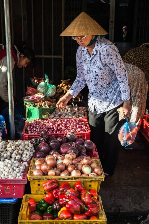 Senior Vietnamese woman in conical hat buying vegetables at the street market, Nha Trang, Vietnam royalty free stock photos