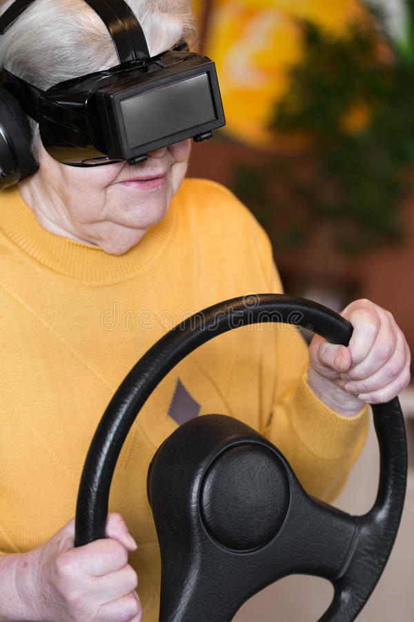 Senior with vr glasses and steering wheel stock photo