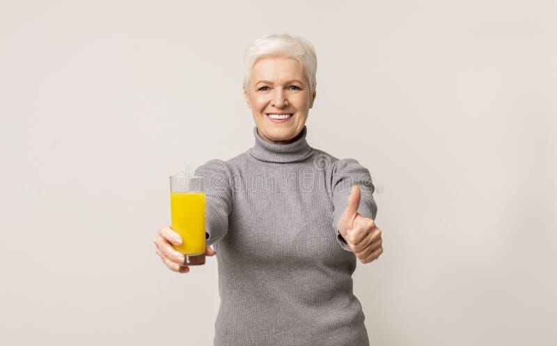 Senior vrouw die sinaasappelsap aanbeveelt, die duim tot camera toont stock foto
