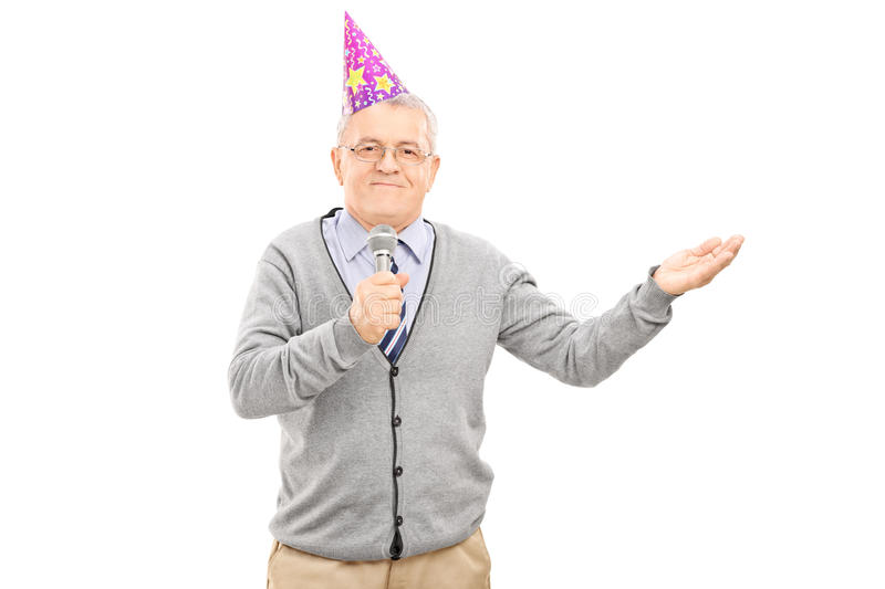 Senior wearing party hat and singing on microphone stock photos