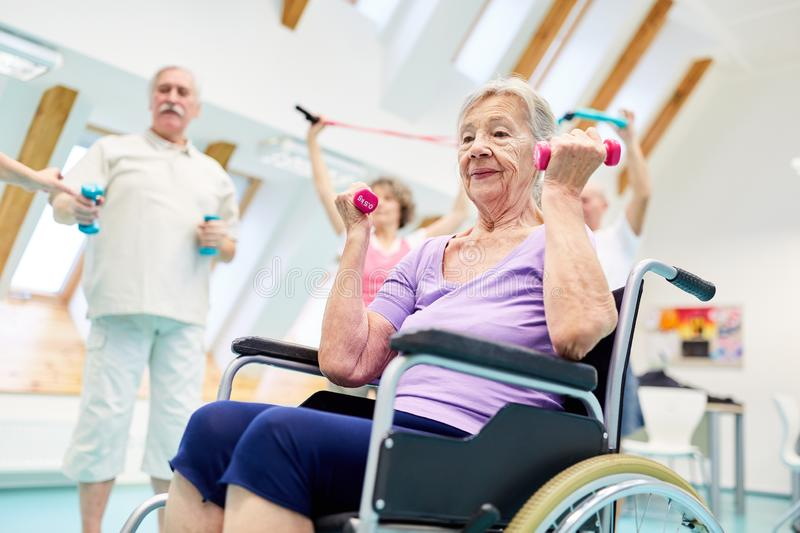 Senior in a wheelchair exercises fitness with dumbbells. Senior women in wheelchair exercises fitness with dumbbells in a rehabilitation group royalty free stock photo