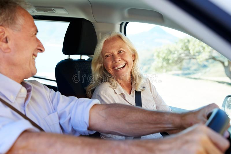 Senior white couple driving in their car, looking at each other, side view, close up royalty free stock photo