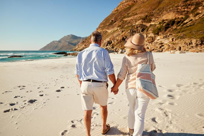 Senior white couple walking on a beach holding hands, back view, three quarter length, close up stock photography