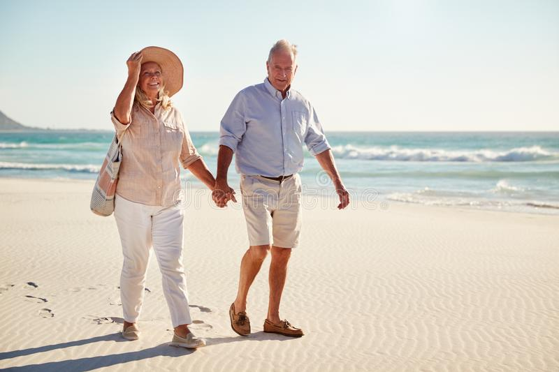 Senior white couple walking on a beach together holding hands, full length, close up stock images