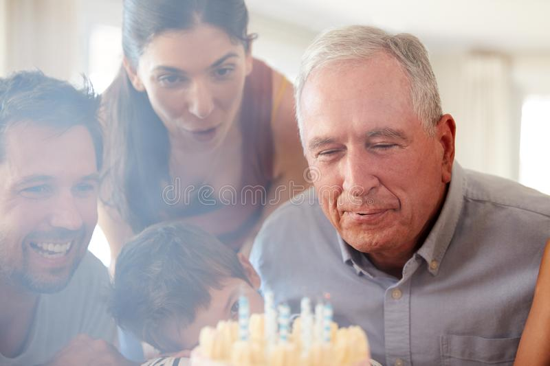 Senior white man celebrating with his family blowing out the candles on birthday cake, close up. Senior white men celebrating with his family blowing out the royalty free stock photos