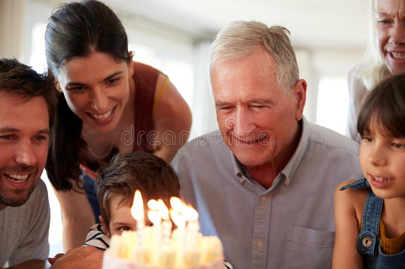 Senior white man and his family celebrating his birthday with cake and lit candles, close up. Senior white men and his family celebrating his birthday with cake stock images