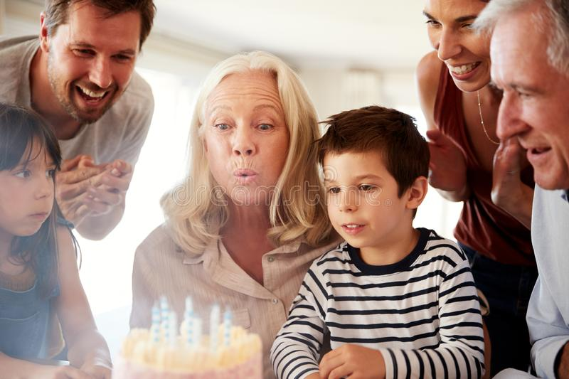 Senior white woman celebrating her birthday with family blowing out the candles on her cake stock photo