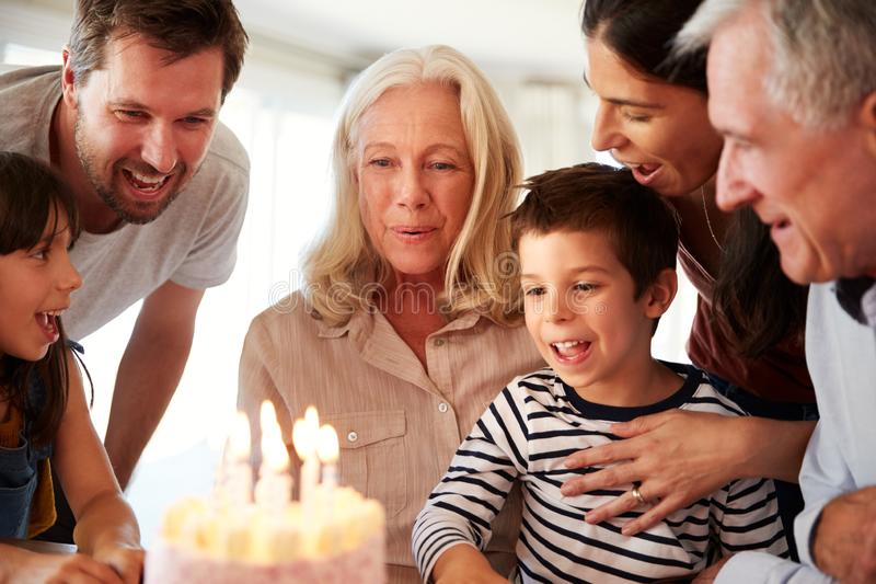 Senior white woman celebrating her birthday with family, blowing out candles on her cake, close up. Senior white women celebrating her birthday with family stock images