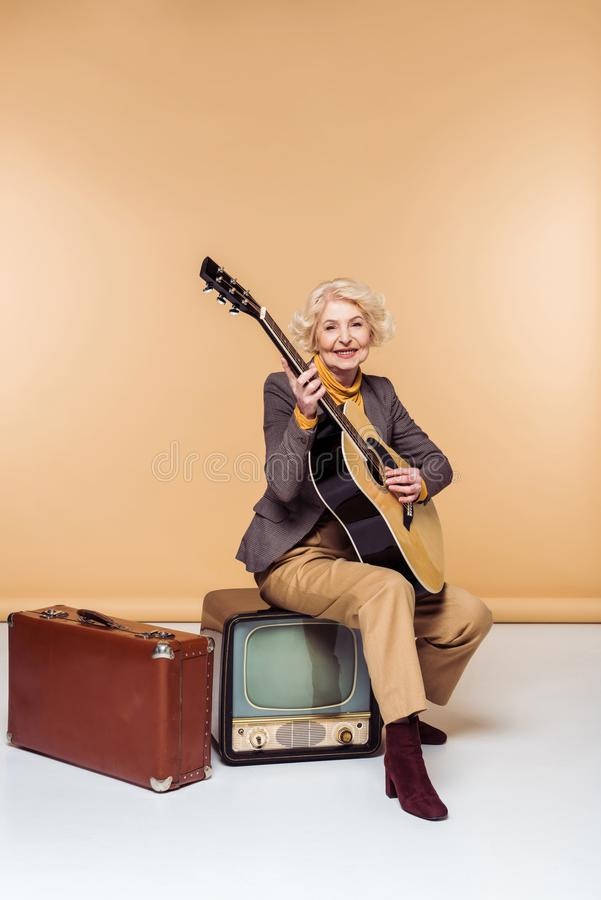 senior woman with acoustic guitar sitting on vintage tv near old royalty free stock images