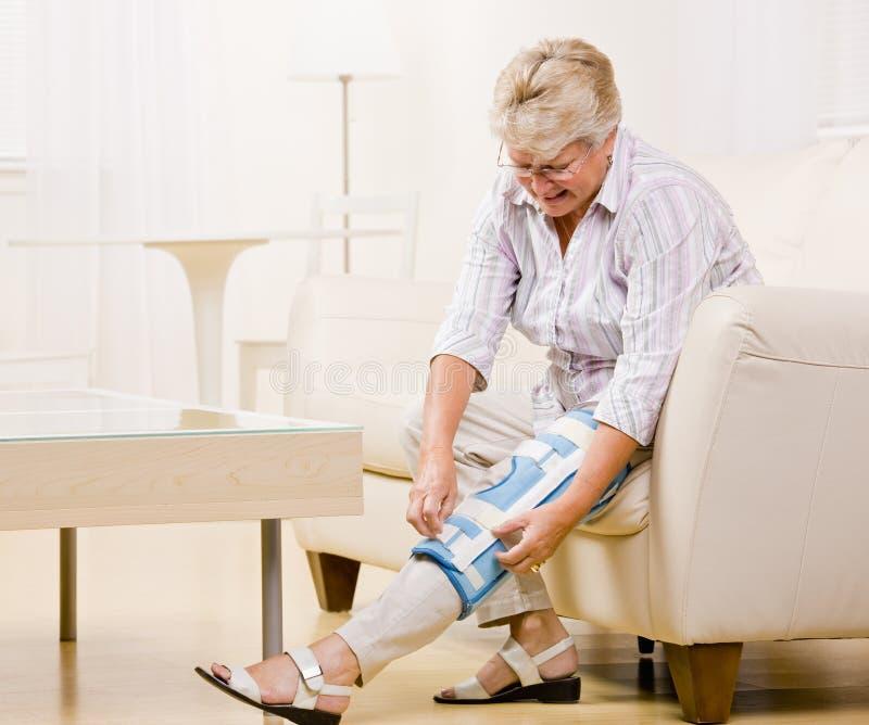 Senior woman adjusting knee brace royalty free stock photos