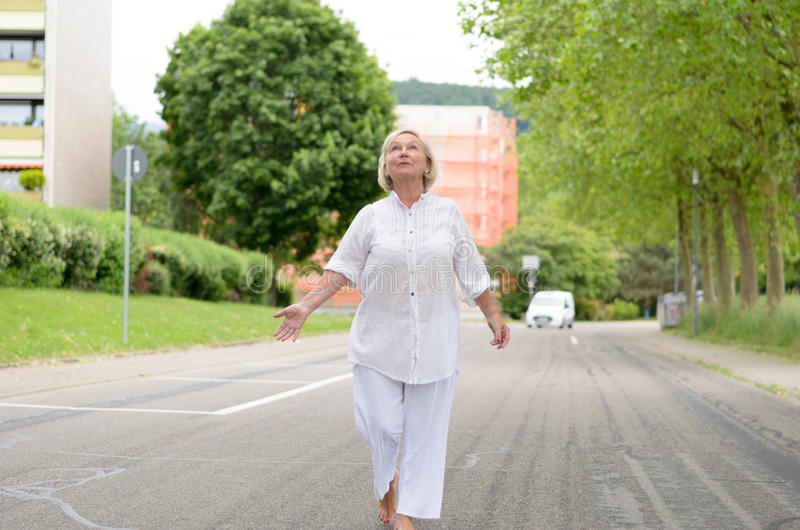 Senior Woman in All White Walking at the Street. And looking to the sky stock image