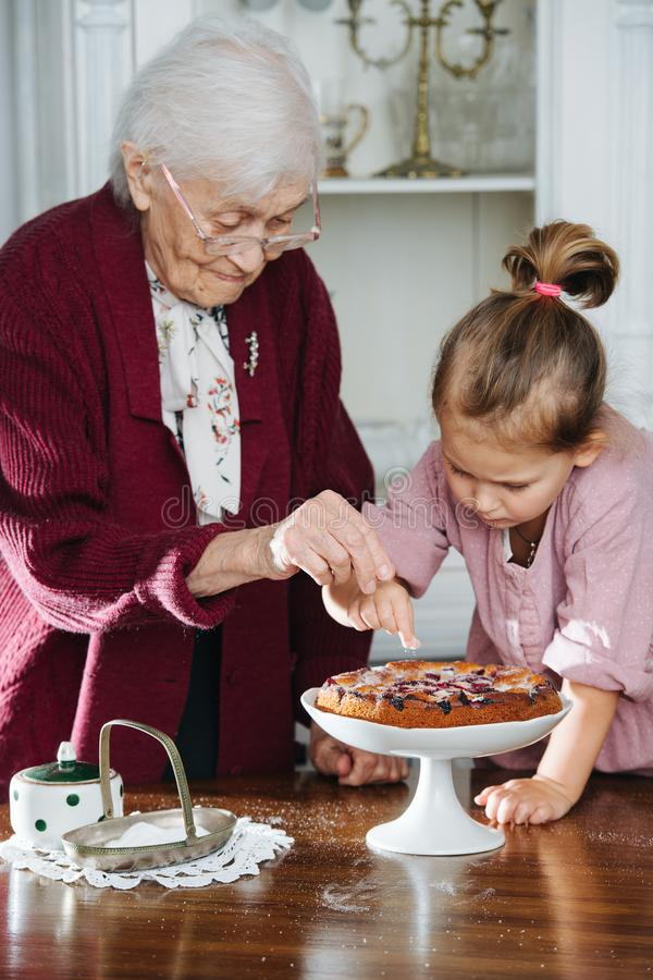 Senior woman along with her granddaughter pouring powdered sugar on tasty pie royalty free stock images