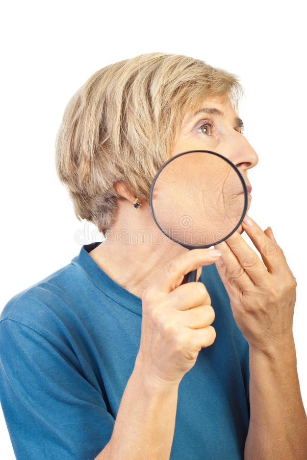 Senior woman analyze her wrinkles with loupe. Senior woman analyze her wrinkles with a magnifying glass and looking away isolated on white background royalty free stock photography