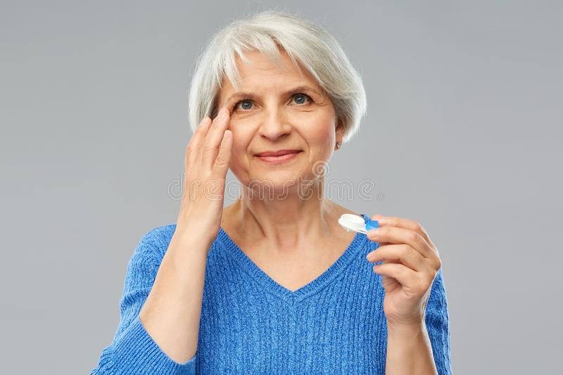Senior woman applying contact lenses. Health, vision and old people concept - senior woman putting on contact lenses over grey background royalty free stock image