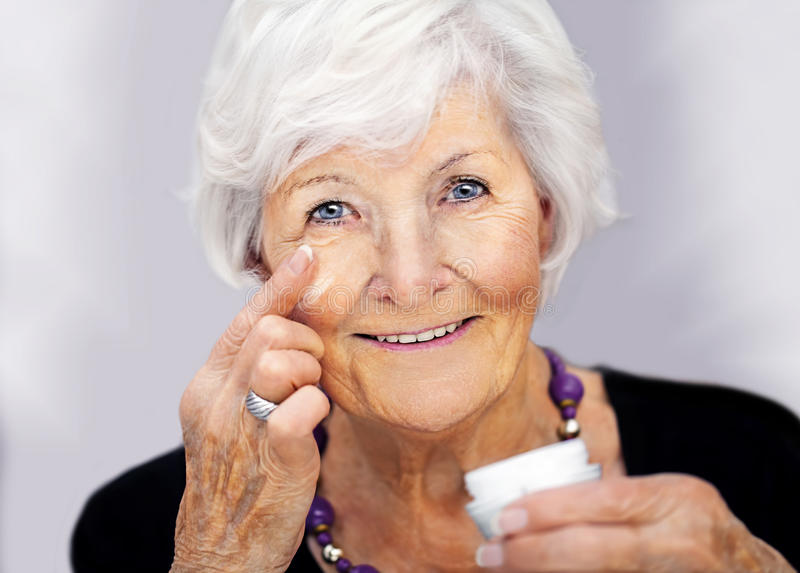 Senior woman applying cream on her face stock images