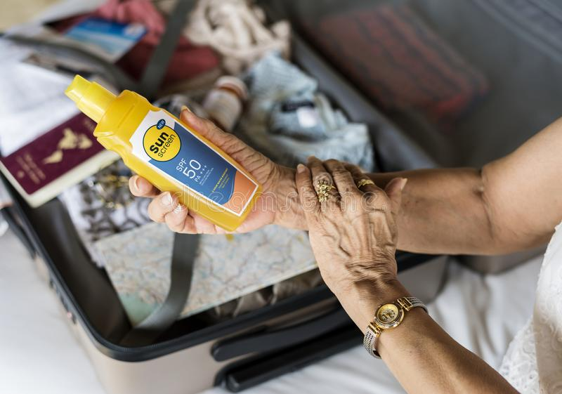 Senior woman applying sunscreen on her arm stock images