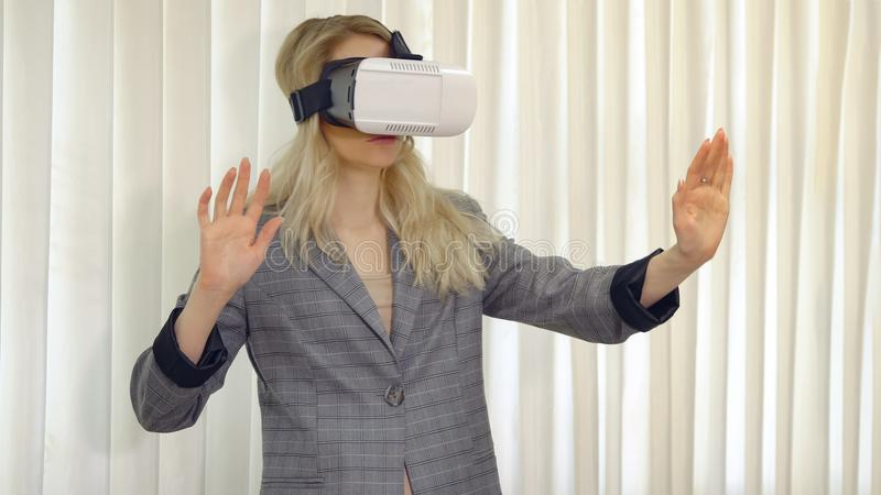 Senior woman architect or client using vr glasses to imagine or design a project standing in the office. stock images