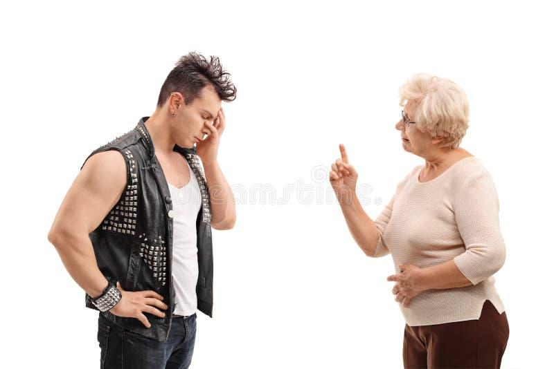 Senior woman arguing with a punker. Senior women arguing with a punker on white background royalty free stock photo