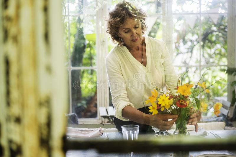Senior woman arranging fresh flowers royalty free stock images
