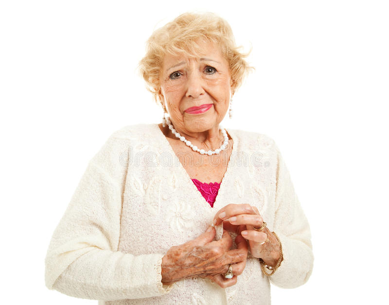 Arthritis - Difficulty with Buttons. Senior woman with arthritis is having trouble buttoning her sweater. Isolated on white royalty free stock images