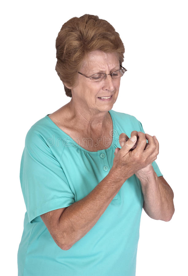 Senior Woman Arthritis Pain in Hands, Growing Old. Mature senior woman suffers from arthritis in her hands. The pain makes her face grimace as the ache hurts her stock photo