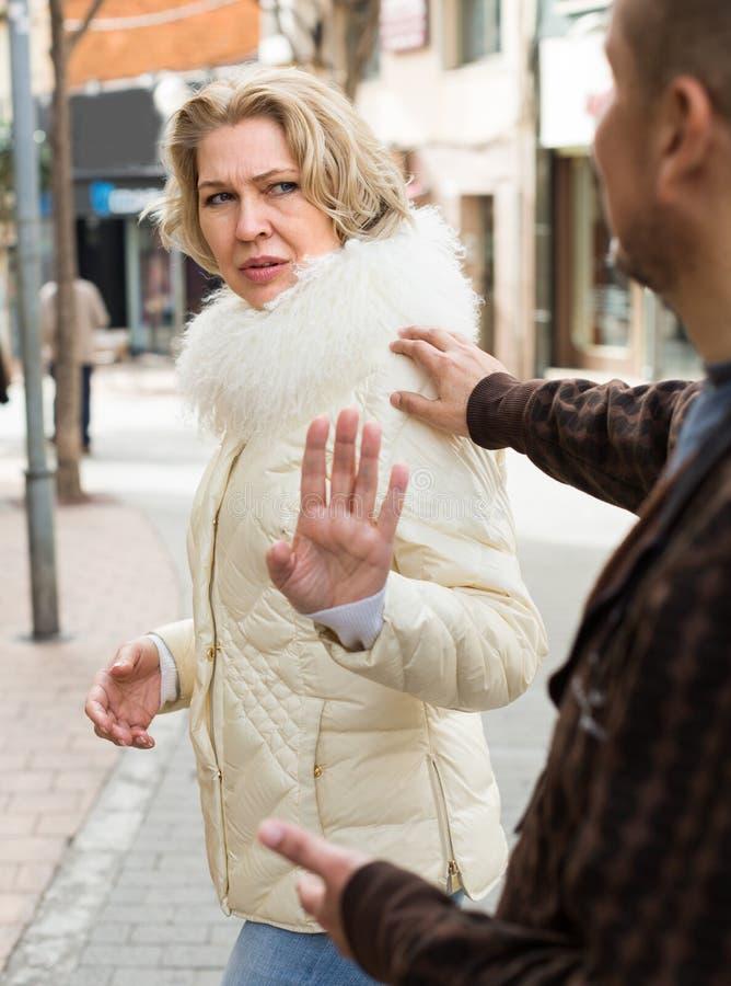 Senior woman asking man. Caucasian senior women asking men not to bother her outdoor royalty free stock photos