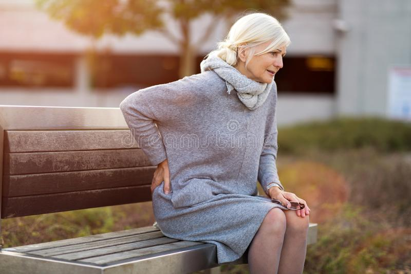 Senior woman with back pain. Having difficulty to get up from the bench stock images