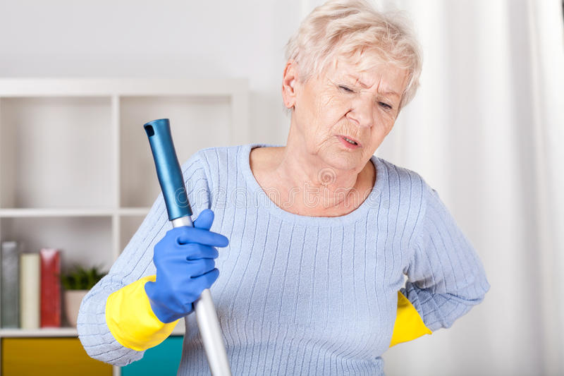 Senior woman with backache. During cleaning royalty free stock image
